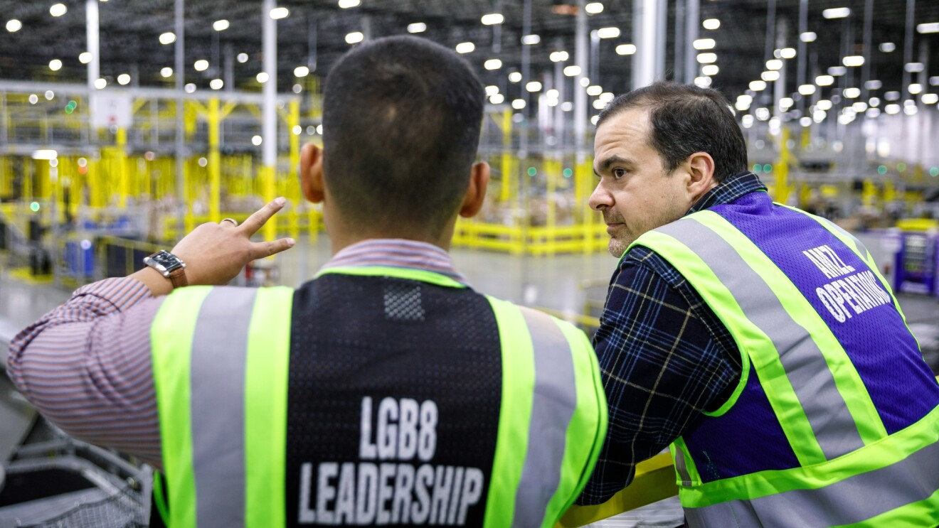 A man wearing a safety vest is explaining something to another man on his right (Jeff Wilke, CEO of worldwide consumer at Amazon), both men are wearing safety vests. In the background, an Amazon fulfillment center.
