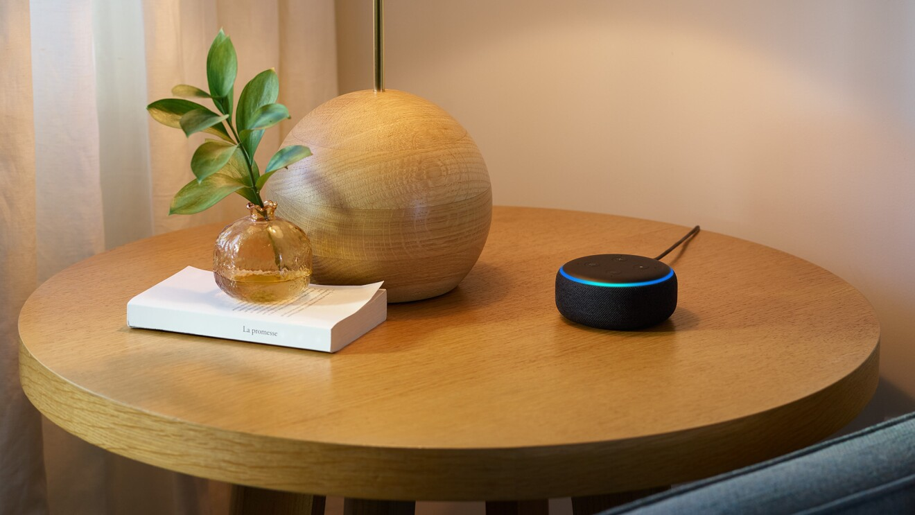 An Echo Dot device sits on a side table, next to a lamp and a small vase holding a branch, on top of a book.