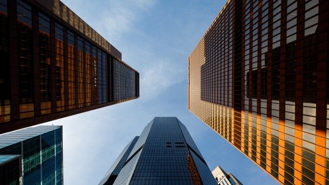 Three skyscrapers reach for the blue sky in Pittsburgh, PA. The perspective is from the ground, looking upward.