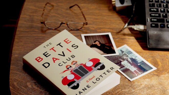 A copy of The Bette Davis Club sits on a tabletop, on top of vintage photographs. In the background rests a pair of glasses, to the right of the book is a laptop computer.