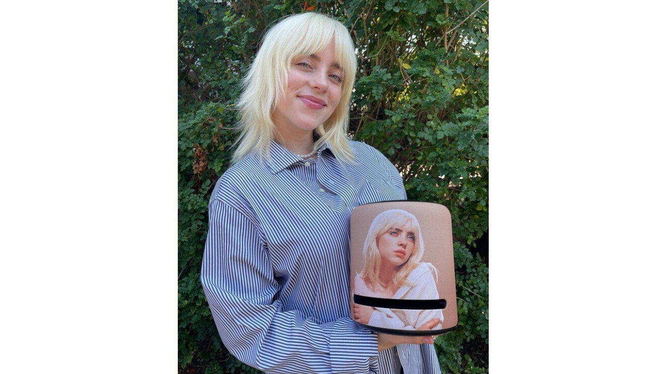 Billie Eilish holds the limited edition Amazon Echo with her face as the design.
