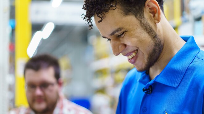 A smiling man is photographed from the side. He wears a blue polo shirt with the Amazon smile logo.