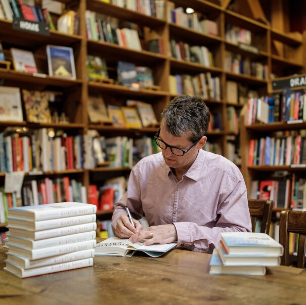 Author signs his book in a bookstore, surrounded by shelves of books