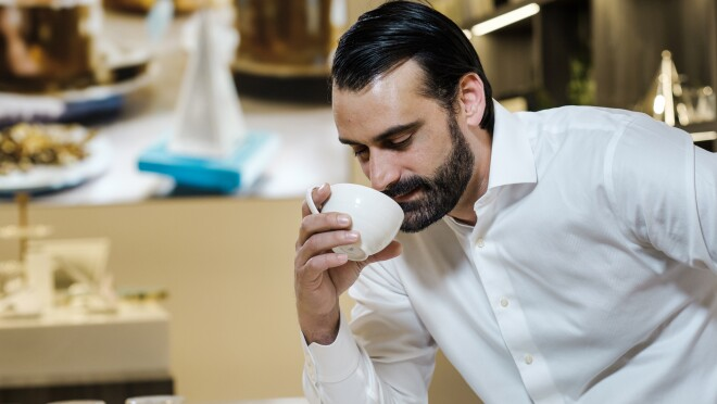 A man holds a tilted cup to his nose to take in the aroma of freshly brewed tea.