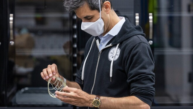 Siegel wears a face mask and inspects a mask prototype.