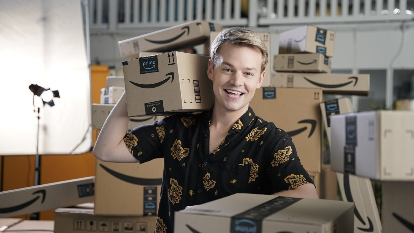A young man wearing a button down shirt smiles at the camera, while holding a few Amazon boxes. Behind him is another, tall stack of Amazon boxes.