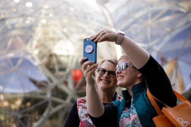 A mother and daughter take a candid selfie in front of The Spheres in downtown Seattle