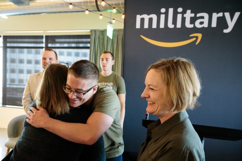 """A man wearing a """"warriors @ Amazon"""" shirt hugs a woman. Next to him, another woman smiles. Behind him, two men stand near an Amazon military sign."""