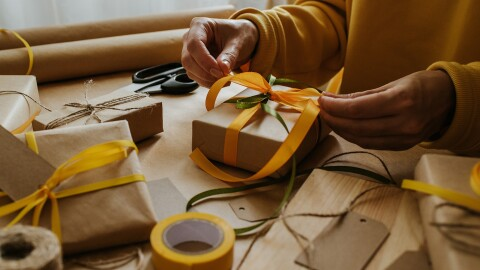 An image of a woman's hands wrapping gifts.