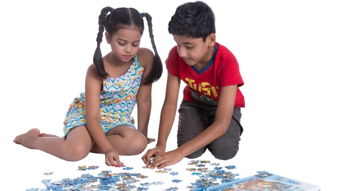 A boy and girl put together pieces of a puzzle