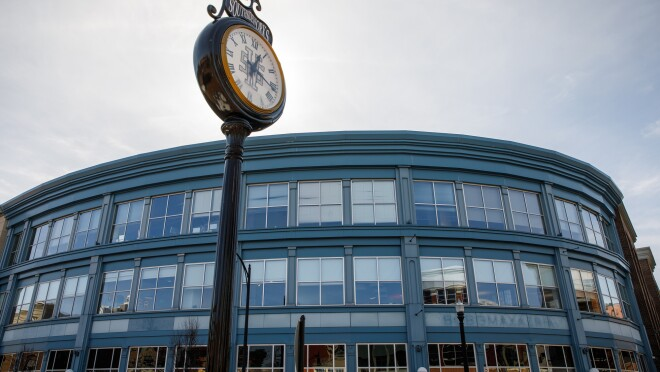 A view of the Amazon Pittsburgh office from the street. The building shows a wall of windows, three stories high. In front of the building is a clock on a light post.
