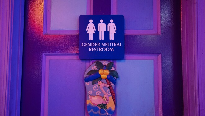 "A door with a sign reading ""gender neutral restroom."""