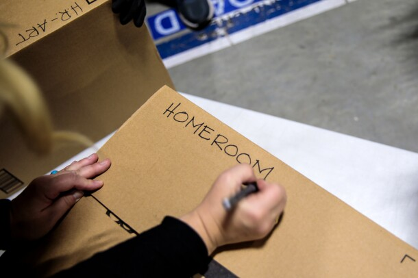 "A person holding a marker in their right hand writes ""homeroom"" in capitalized block letters on a cardboard box."