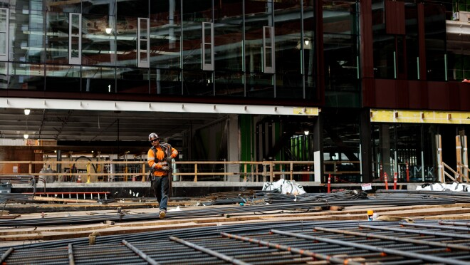 A man in a construction helmet and orange safety jacket is photographed at a construction site on Amazon's campus in Seattle, WA. He is walking across an unfinished floor covered in rebar.