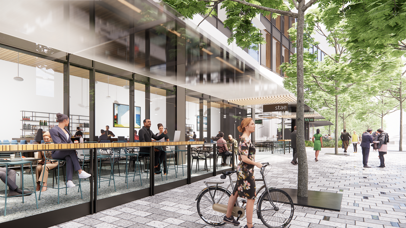A rendering of the future Bellevue 600 site shows a woman wearing a floral bicycle and her bicycle. Behind her, people enjoy an open-air patio.