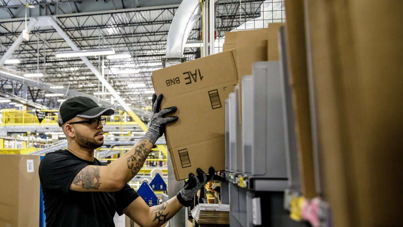 A man in a baseball cap, glasses, and a black T-shirt, working in an Amazon Fulfillment Center lifts a flat cardboard box.