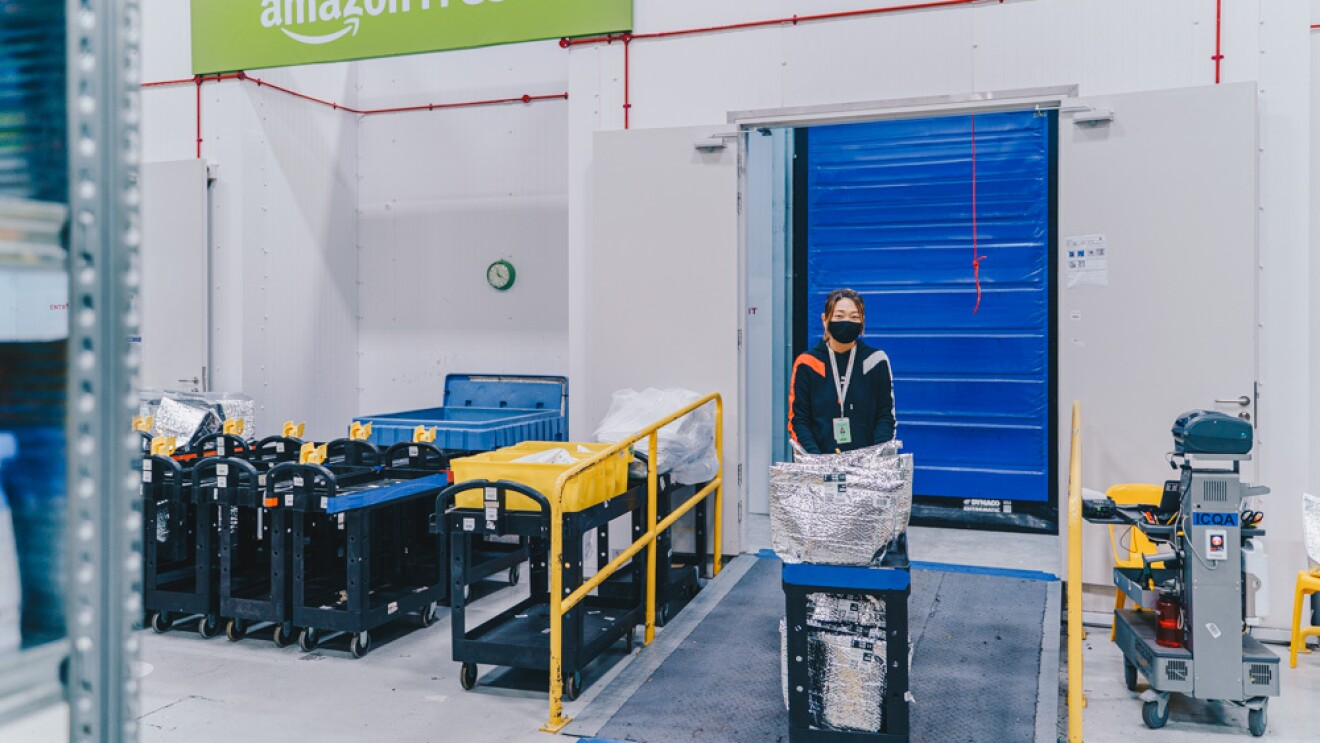 An employee pushing a trolley out of the chiller and freezer