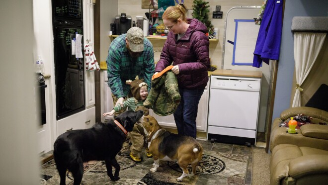 A man, a woman, and a toddler stand inside a home. The woman holds a small jacket. Two dogs are in the foreground.