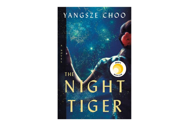 "Book cover for ""The Night Tiger"" by Yangsze Choo, shows a woman leaning on a doorway, her arm bent as she leans, wearing a short-sleeved frock, with a flower in her tied-back hair. In front of her is a darkened blue landscape with flashes of light."