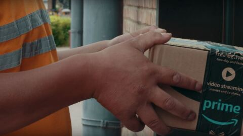 An Amazon delivery driver hands over a package to a customer. The box tape features the smiling Prime logo and video streaming icon.