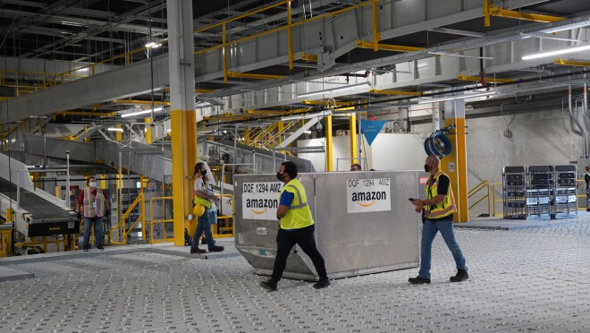 An image of a large metal container in the middle of an Amazon sortation center. There are employees in safety vests walking around the container.