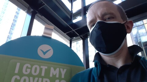 "A man wearing a mask and a collared shirt sits in front of a sign that says ""I got my COVID-19 vaccine."""