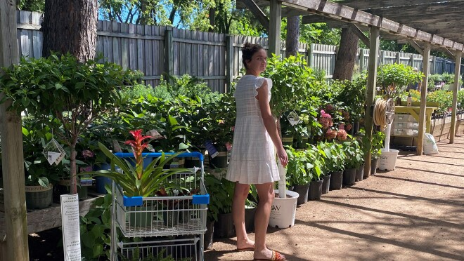 An image of a woman standing in front of a row of plants at a garden store. There is a shopping cart in front of her with a plant in it.