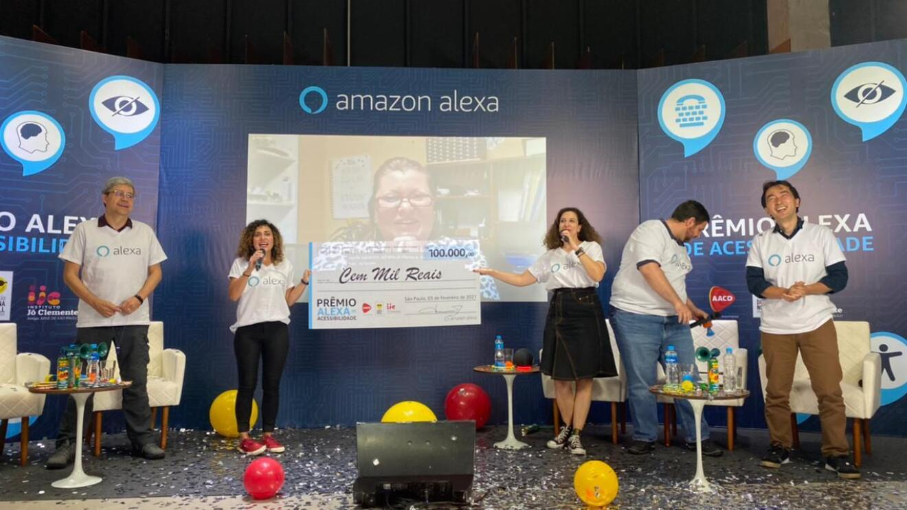 Thais, along with her colleagues, standing on a stage and honoring a winner of the Alexa Accessibility Award.