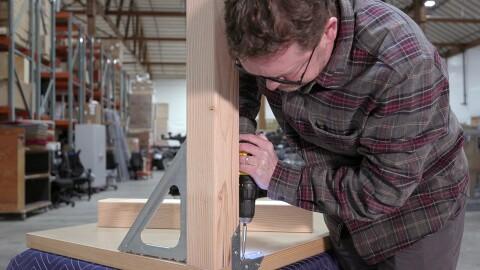 Amazon employee Nico Lovejoy builds a door desk.