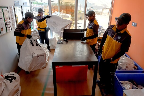 Four men in uniforms with Amazon logos stand around a table. One man carries a large plastic bag. Another man shakes an empty plastic bag in preparation for leading it. Bins and packages are on the floor at the right side of the image.