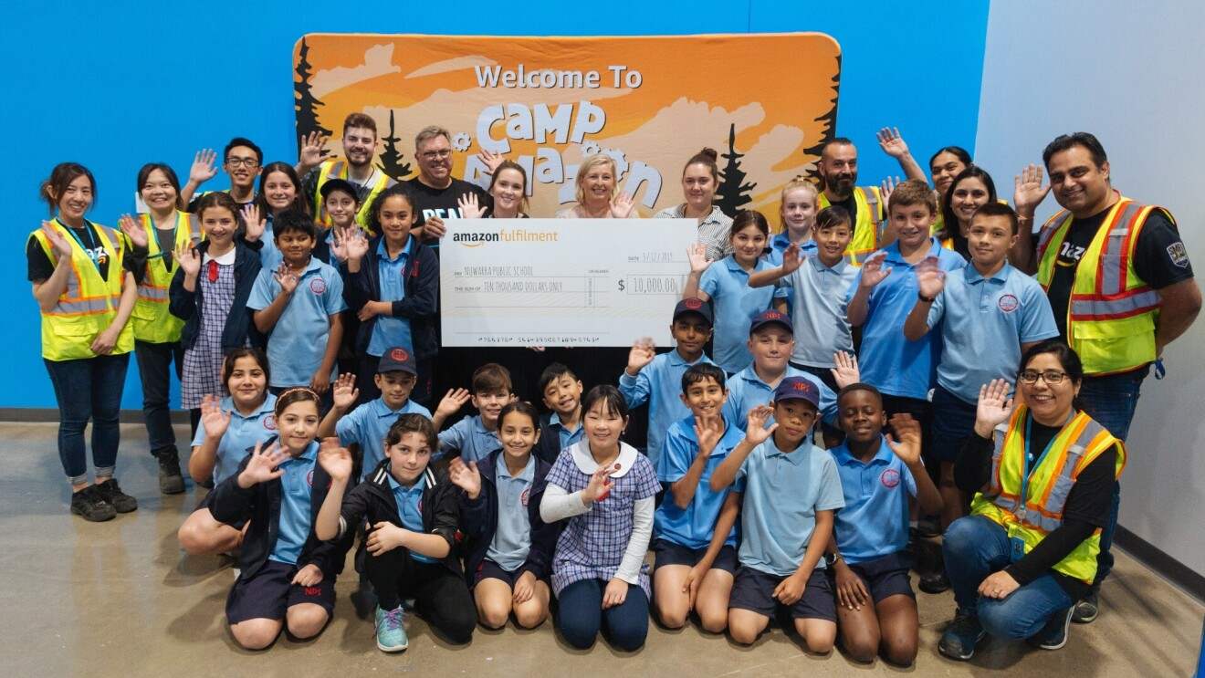 A group of kids, their teachers and Amazon Camp staff wave and smile for the camera holding a check for $10,000 from Amazon.