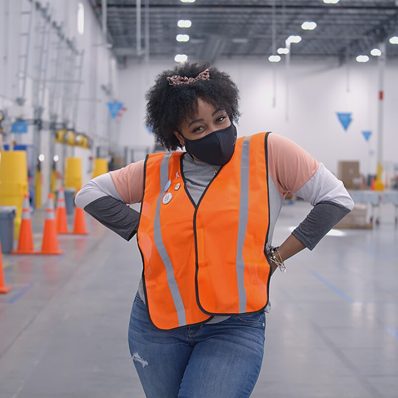 a Black woman who is an Amazon employee looks at the camera. She is wearing a face mask.