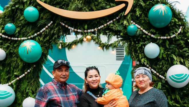 An image of a family smiling for a photo in front of a large wreath. There is a baby in the photo wearing an orange pumpkin costume.