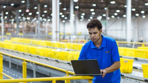 A man in a blue polo shirt works on a laptop in a large, high-ceilinged space. Yellow plastic totes are behind him and stretch into the distance.