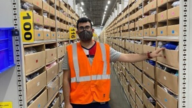 Shams Hussamy, an Amazon Associate, stands for a photo in the fulfillment center where he works in Ontario.