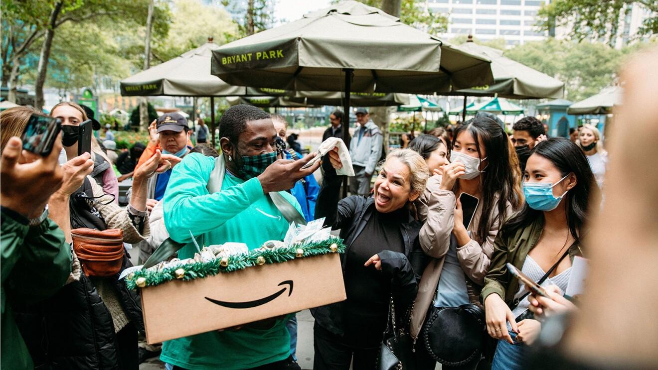 An image of a man passing out treats to an excited crowd. The box with the treats has the Amazon logo on it. The man is wearing a green Amazon shirt and a black and green checkered mask.