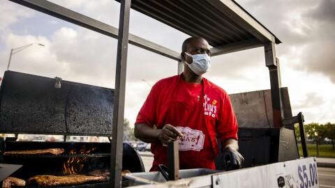 A man stands in front of an outdoor smoker. He wears a mask and holds products to prepare meals for customers.