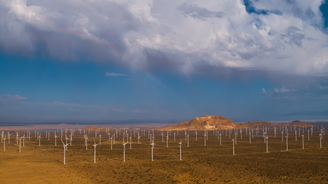 An aerial view of a wind farm in a mountainous desert landscape.