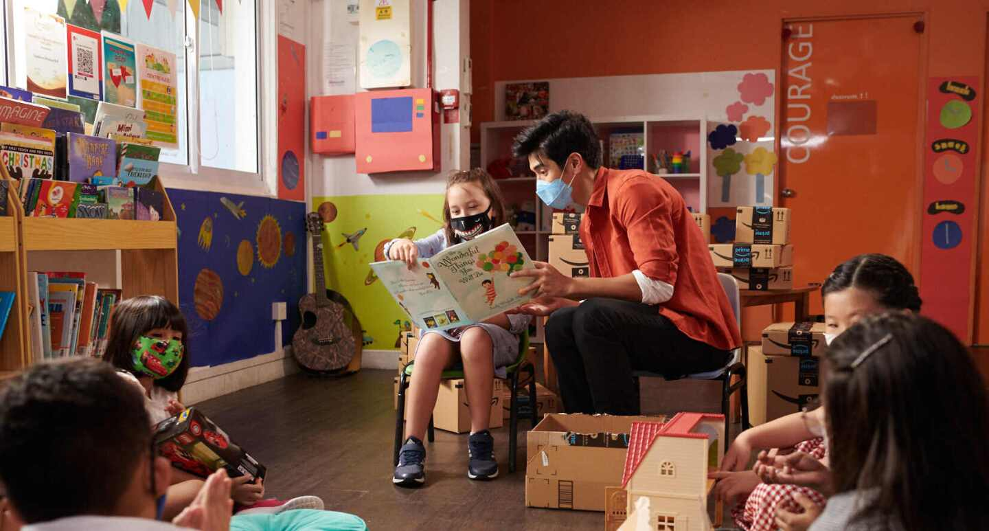 Nathan Hartono sits and reads a book with one of the beneficiaries