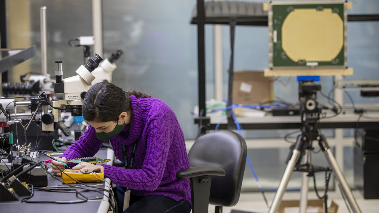 A woman sits at a table while working on an engineering project for Project Kuiper.