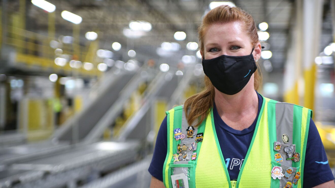 A woman wearing a mask and a safety vest stands in an Amazon fulfillment center, looking at the camera.
