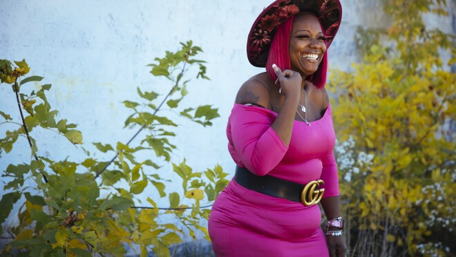 Auhzha Wright smiles as she models her pink dress and custom-made hat while standing outside in front of lush landscaping.