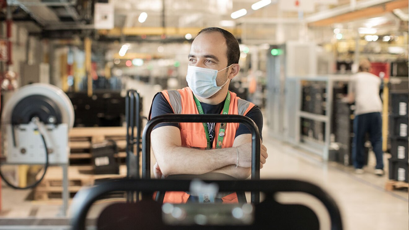 Amazon associate Mohanad wears a mask and safety vest inside an Amazon fulfillment center