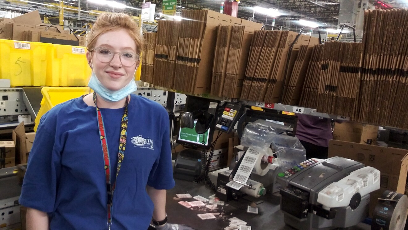 A woman stands at a workstation stocked with cardboard boxes and labeling machines. She has a protective mask on, ready to cover her mouth and nose.