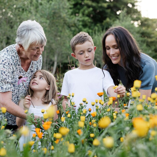 Three generations of a family stand in a floral garden and engage with eachother.