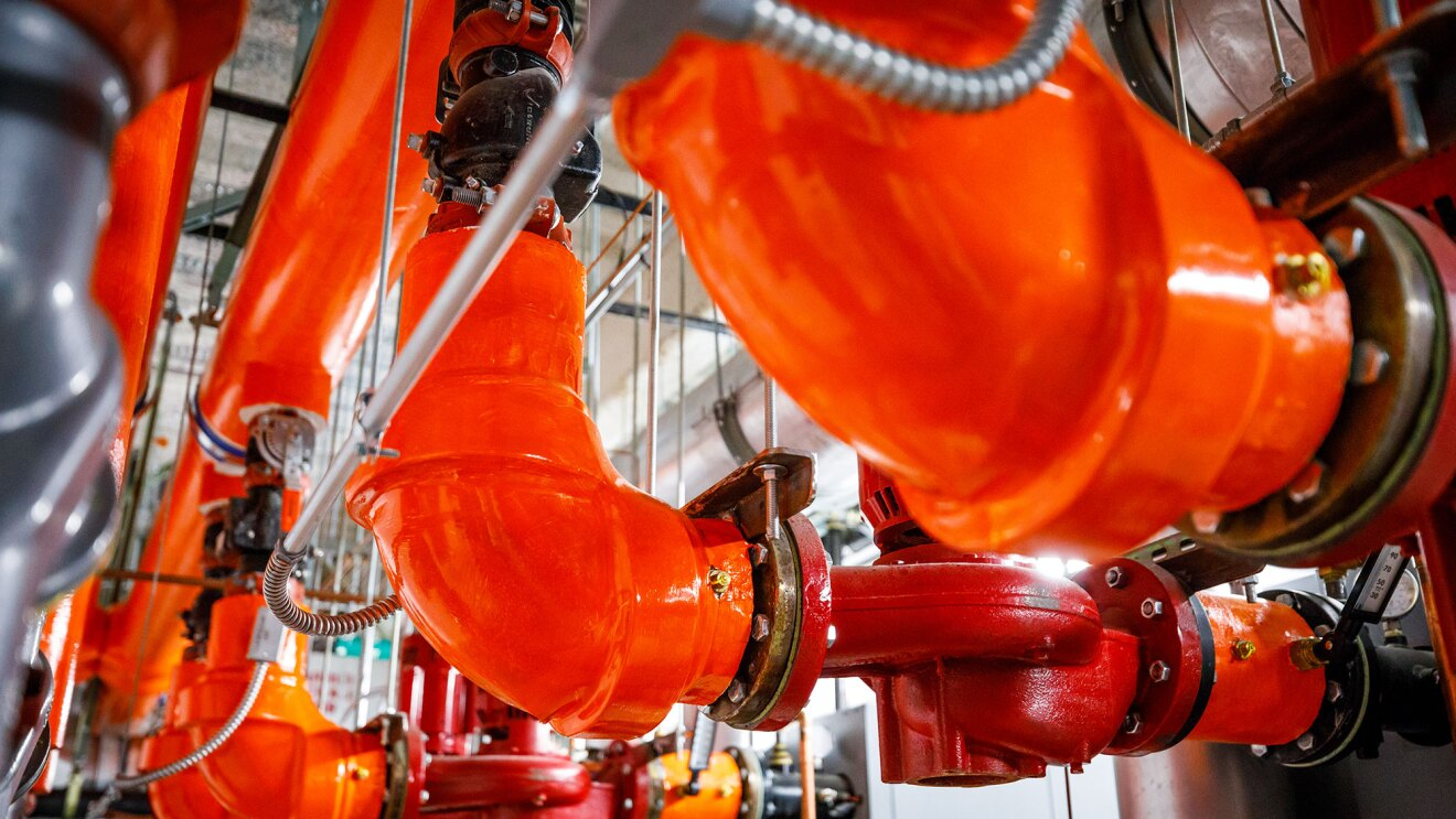 Three bright orange steam pipes are seen in a mechanical room under the Westin Seattle.