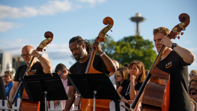 Three members of the Amazon Symphony Orchestra are seen playing their cellos. Each wears a black tee shirt, and stands behind a music stand. Behind the musicians, a crowd of attendees is visible.