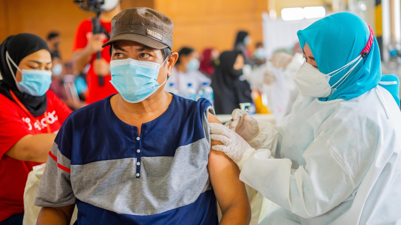 An Indonesian man is being vaccinated by a nurse in a vaccination centre