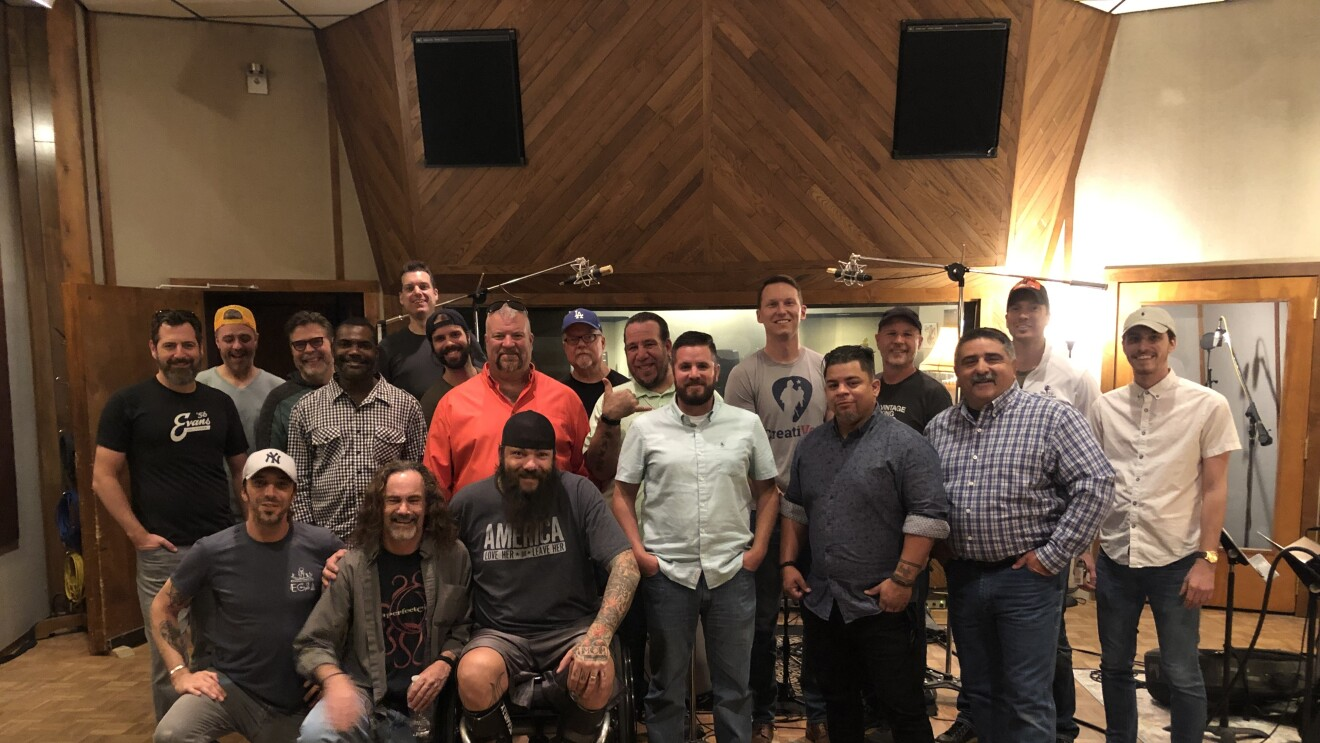 A group of men gather inside a recording studio (image taken before COVID-19 pandemic)