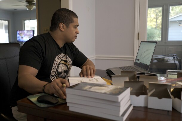 A man sits at a desk in front of a laptop computer. A book is open in front of him.  A stack of books is in the foreground of the image.